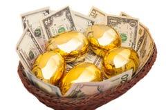 金黄鸡蛋和美元在篮子 免版税库存图片
