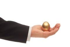 金黄鸡蛋在手中 免版税库存照片