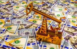 金黄Pumpjack和溢出的油在金钱 3d场面 免版税库存图片
