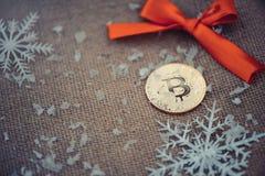金bitcoin 在圣诞节背景红色弓和雪花的隐藏货币bitcoin 问题和企业成长 新年` s 免版税库存图片