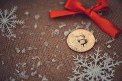 金bitcoin 在圣诞节背景红色弓和雪花的隐藏货币bitcoin 问题和企业成长 新年` s 免版税库存照片