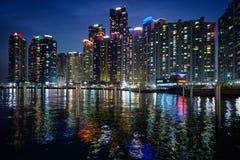 釜山小游艇船坞在夜illluminated的城市摩天大楼 库存照片