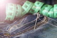 针和螺纹在牛仔裤,磁带 免版税库存图片
