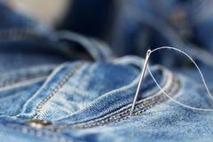 针和螺纹在牛仔裤 免版税库存照片