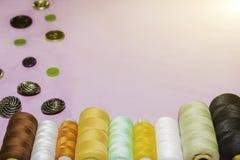 针线和剪裁概念-缝合的螺纹按钮、短管轴和布料 免版税库存照片