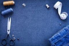 针线和牛仔裤在深蓝牛仔裤织品背景  免版税库存图片