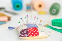 针线,工艺,缝合和剪裁概念-与白色按钮的宏指令,五颜六色被缝的针垫和美丽 免版税库存图片