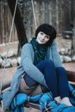 针织品的美丽的少妇坐摇摆 免版税库存照片