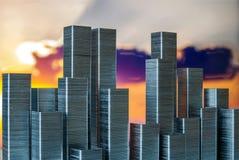 钉书针准备形成在日落背景的城市地平线 免版税库存图片