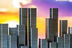 钉书针准备形成在日落背景的城市地平线 免版税图库摄影
