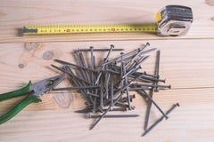 钉子、一卷测量的磁带和钳子 库存照片