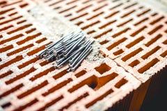 钉子和工具在建造场所、砌砖工和灰浆 新的建筑工地墙纸,木匠业 库存照片