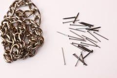 钉子和链子在白色桌上 图库摄影