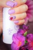 钉子春天样式设计在手中一个罐头防臭剂 库存图片