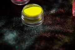 钉子的黄色粉末在黑背景 免版税库存照片