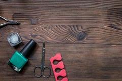 钉牢有修指甲器的艺术家书桌和手关心木背景顶视图大模型的指甲油 免版税库存照片