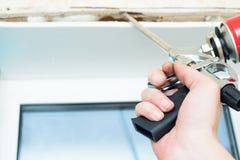 钉牢枪使用在窗口附近安装修剪 免版税库存照片
