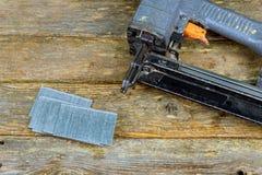 钉牢枪和钉子在松木桌上 免版税库存照片