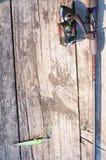 钓具-渔转动,勾子和诱剂在木码头 免版税图库摄影