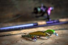 钓具-渔转动,勾子和诱剂在轻的木背景 顶视图 库存图片
