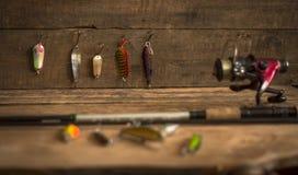 钓具-渔转动,勾子和诱剂在轻的木背景 顶视图 免版税库存图片