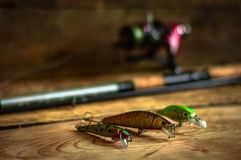 钓具-渔转动,勾子和诱剂在轻的木背景 顶视图 免版税图库摄影