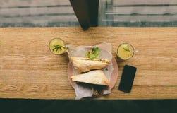 钓鱼三明治和蒜味咸腊肠,与茶手机 库存照片