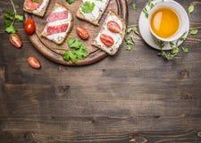 钓鱼三明治和蒜味咸腊肠,与茶边界,地方文本木土气背景顶视图的 库存照片