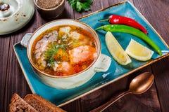 钓鱼与三文鱼的汤和虾、莳萝、土豆、柠檬、胡椒和面包在黑暗的木背景,健康食物 图库摄影