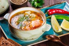 钓鱼与三文鱼的汤和虾、莳萝、土豆、柠檬、胡椒和面包在黑暗的木背景, 免版税库存图片