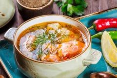 钓鱼与三文鱼的汤和虾、莳萝、土豆、柠檬、胡椒和面包在黑暗的木背景, 免版税库存照片
