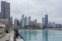 钓鱼与从海军码头的芝加哥地平线的人 免版税库存照片