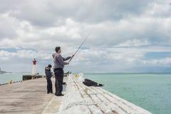 钓鱼与标尺的少年和流利地读出港口墙壁 库存图片