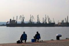 钓鱼与标尺的渔夫在码头在海口在一温暖的无风秋天天 免版税库存图片