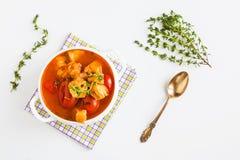 钓鱼与鳕鱼、蕃茄、葱、大蒜和麝香草的汤在白色桌,顶视图上的碗 库存图片