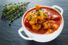 钓鱼与鳕鱼、蕃茄、葱、大蒜和麝香草的汤在黑石背景的白色碗 免版税库存图片