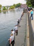 钓鱼为三文鱼的人们在Oswego河 免版税库存照片