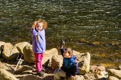 钓鱼为在Douthat湖的鳟鱼的孩子夫妇  图库摄影