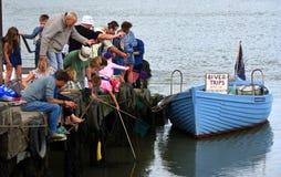 钓鱼为螃蟹的人们跳船 免版税库存图片