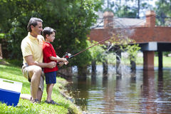 钓鱼他的河儿子的父亲 免版税图库摄影
