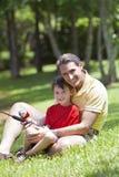 钓鱼他的河儿子的父亲 免版税库存图片