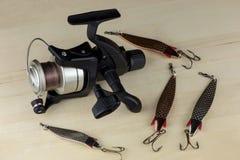 钓鱼卷轴和钓鱼木表面上的诱剂 免版税库存照片