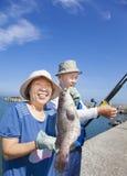 钓鱼和显示大石斑鱼鱼的资深夫妇 免版税库存图片