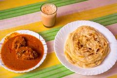 钓鱼咖喱、parotha和茶-传统南印地安食物 库存照片