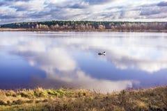 钓鱼在一个大湖的单独渔夫在秋天 免版税库存图片