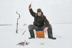 钓鱼在冬天 钩在冰的渔夫鱼 库存照片