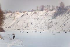 钓鱼在冰的全部人在冬天 免版税库存照片
