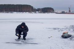 钓鱼在冻河的冬天钓鱼竿的黑暗的衣裳的年长渔夫 免版税库存照片