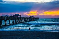 钓鱼在和在码头下在黎明 免版税库存照片