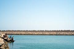 钓鱼在小游艇船坞的波浪破碎机的男孩在与平的海和清楚的天空的一镇静天 库存照片